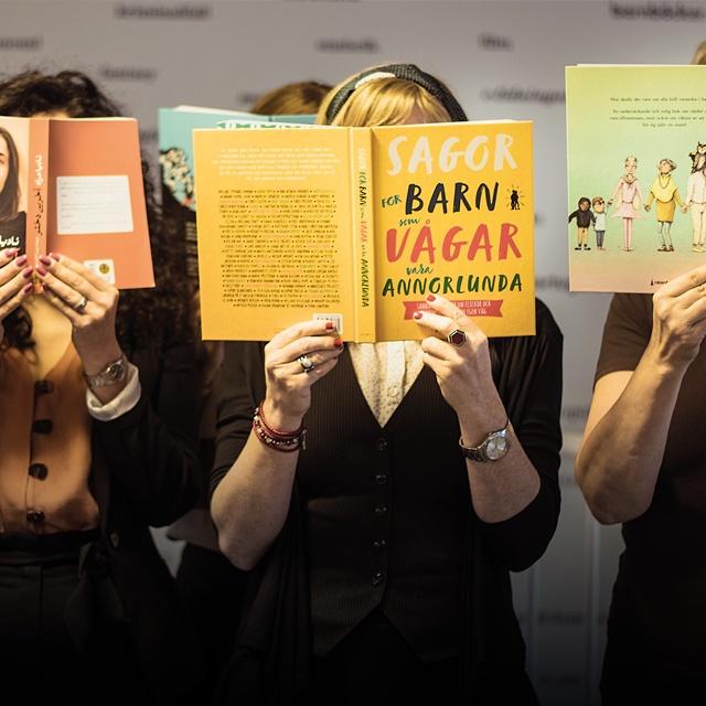 kvinnor som håller böcker framför ansiktet